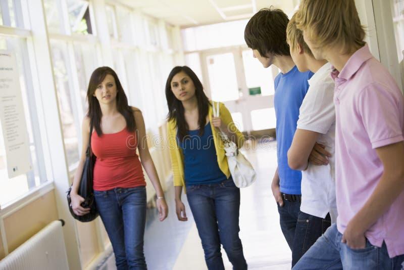 Studenti di college maschii che guardano gli allievi femminili immagini stock