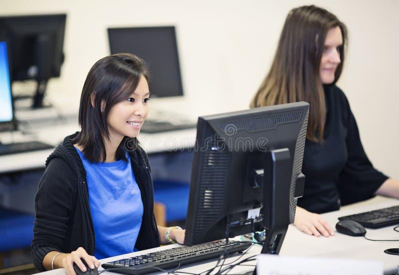 Studenti di college in un laboratorio del computer fotografie stock libere da diritti