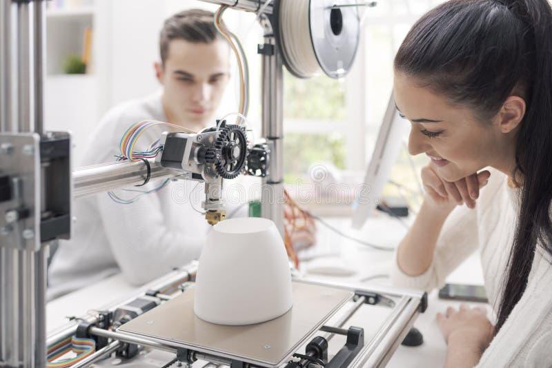 Studenti di ingegneria che utilizzano una stampante 3D nel laboratorio fotografie stock libere da diritti