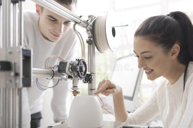 Studenti di ingegneria che utilizzano una stampante 3D nel laboratorio immagini stock