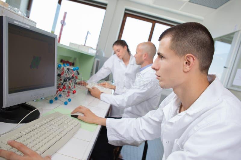 Studenti di ingegneria in laboratorio facendo uso del computer fotografie stock