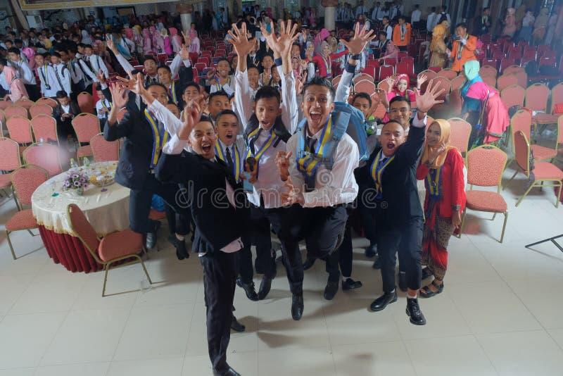 Studenti divertendosi sulla loro graduazione immagine stock libera da diritti