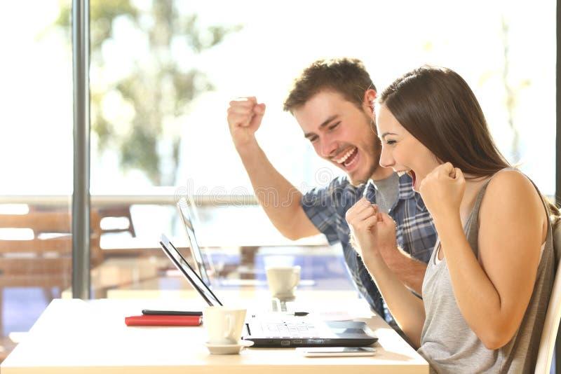 Studenti euforici che guardano i risultati dell'esame immagine stock