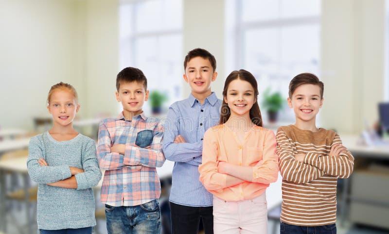 Studenti felici alla scuola sopra il fondo dell'aula immagini stock libere da diritti