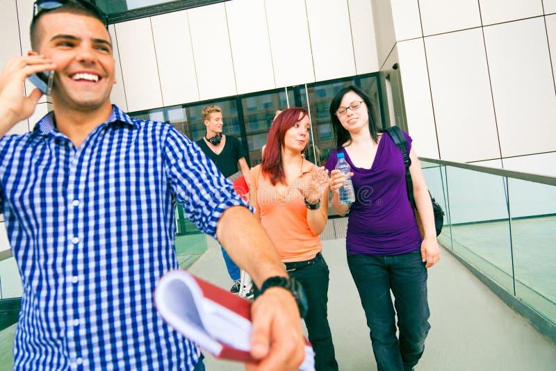 Studenti felici che camminano dall'istituto universitario fotografia stock