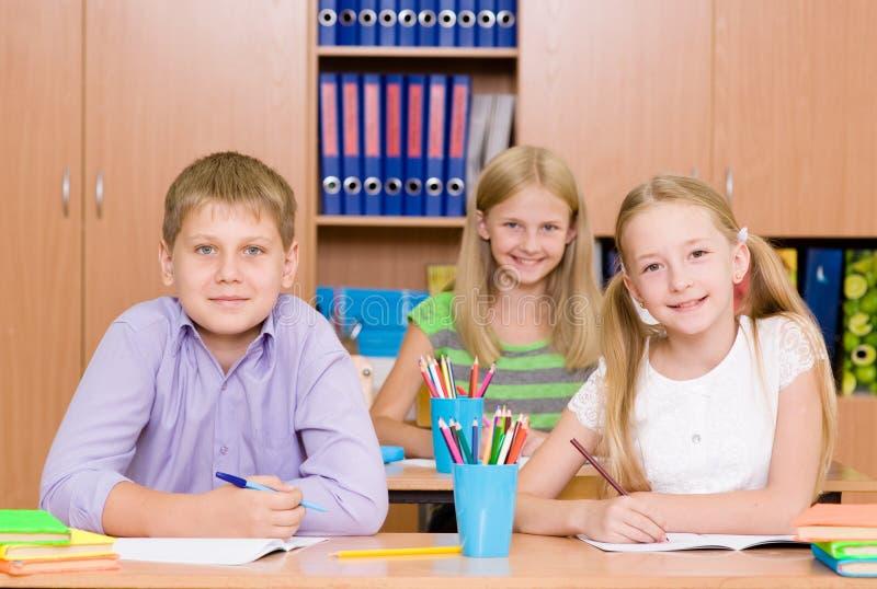Studenti felici che si siedono ai loro scrittori nell'aula fotografia stock