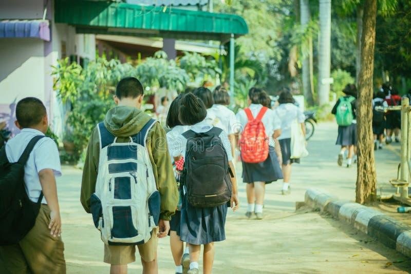 Studenti felici divertendosi sulla via dopo la scuola immagini stock libere da diritti