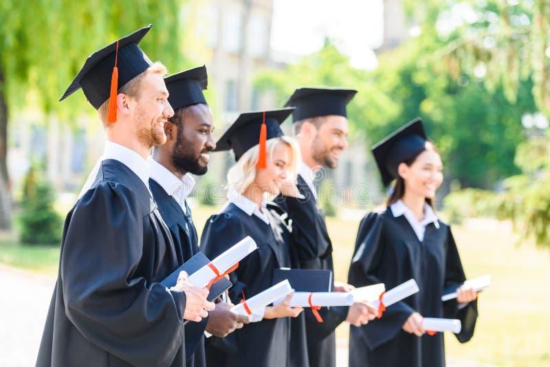 studenti graduati felici in capi e nella tenuta dei cappelli fotografie stock libere da diritti