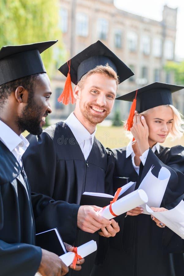 studenti graduati multietnici felici in capi immagine stock libera da diritti