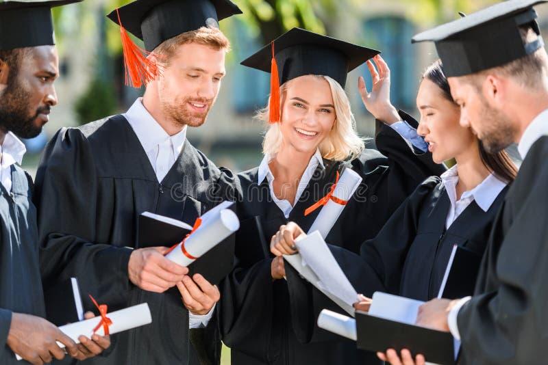 studenti graduati multietnici sorridenti in capi immagini stock