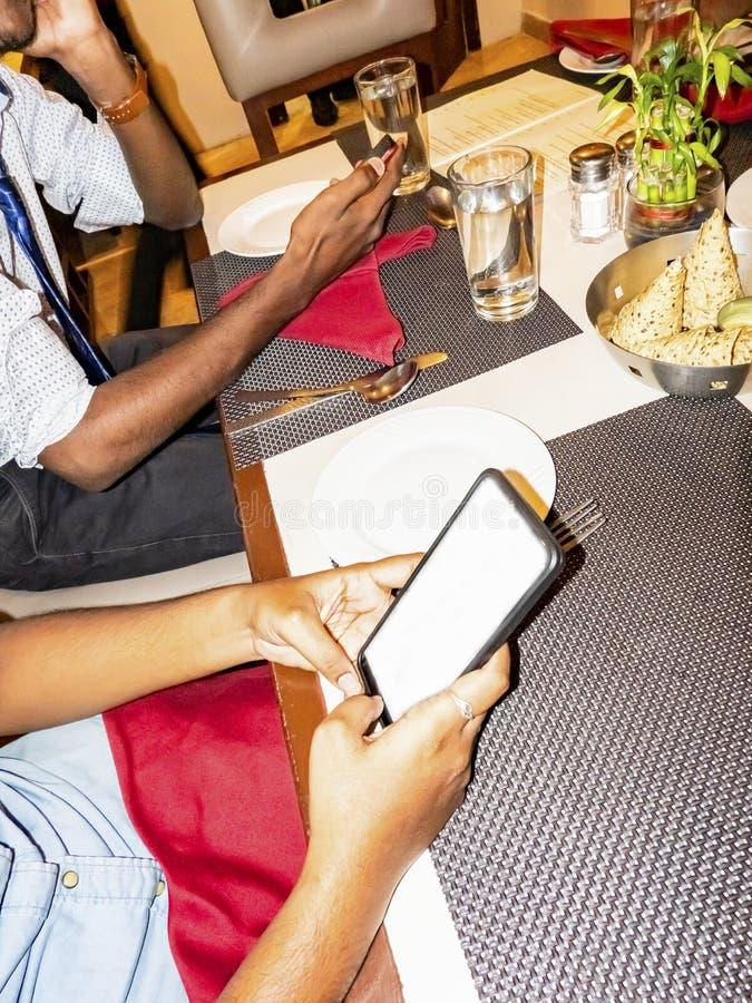 Studenti indiani degli adulti della donna del giovane al ristorante con gli smartphones immagini stock libere da diritti