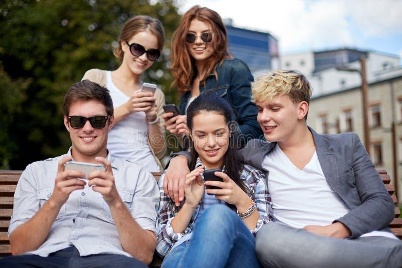 Studenti o adolescenti con gli smartphones alla città universitaria immagini stock