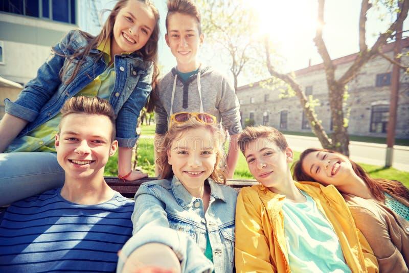 Studenti o amici adolescenti felici che prendono selfie immagine stock libera da diritti