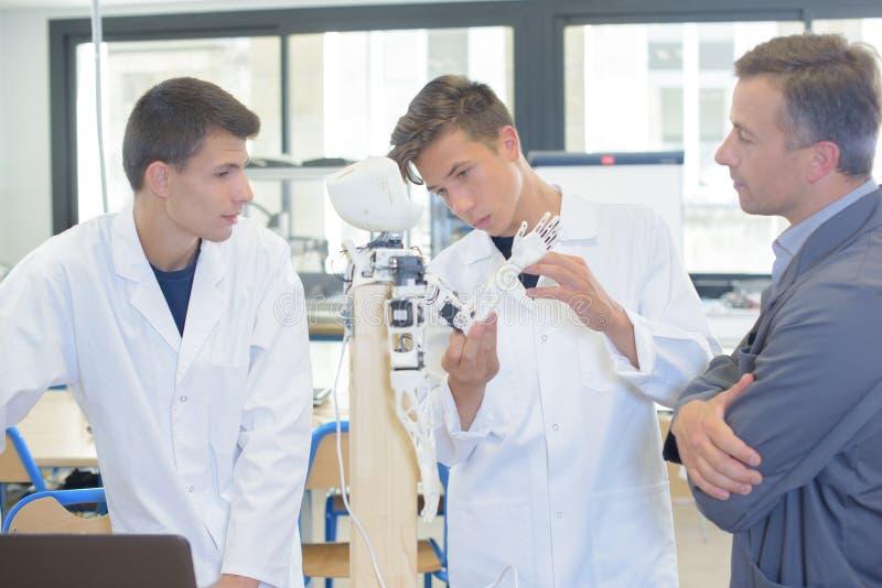Studenti scientifici che mostrano apparecchio elettronico immagine stock libera da diritti