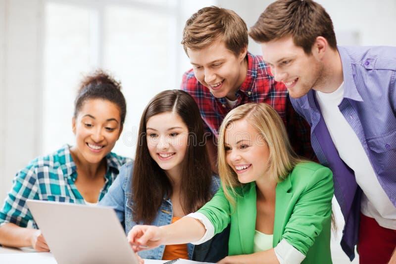 Studenti sorridenti che esaminano computer portatile la scuola immagine stock