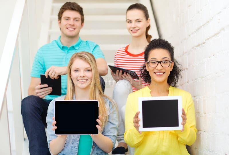 Studenti sorridenti che mostrano a pc della compressa schermo in bianco immagini stock