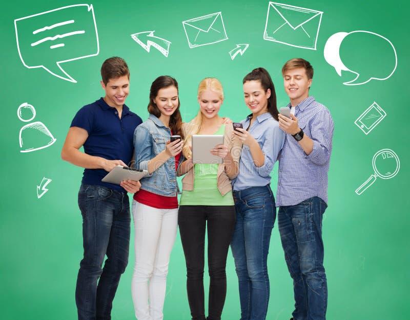 Studenti sorridenti con i pc e gli smartphones della compressa immagini stock libere da diritti