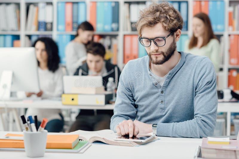Studenti universitari che per mezzo di una compressa immagini stock