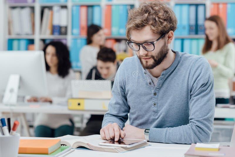 Studenti universitari che per mezzo di una compressa immagini stock libere da diritti