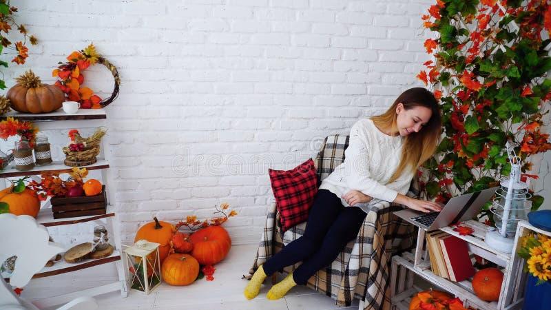 Studentin Corresponds With Friends auf Internet, unter Verwendung des Laptops und des Sitzens stockbild