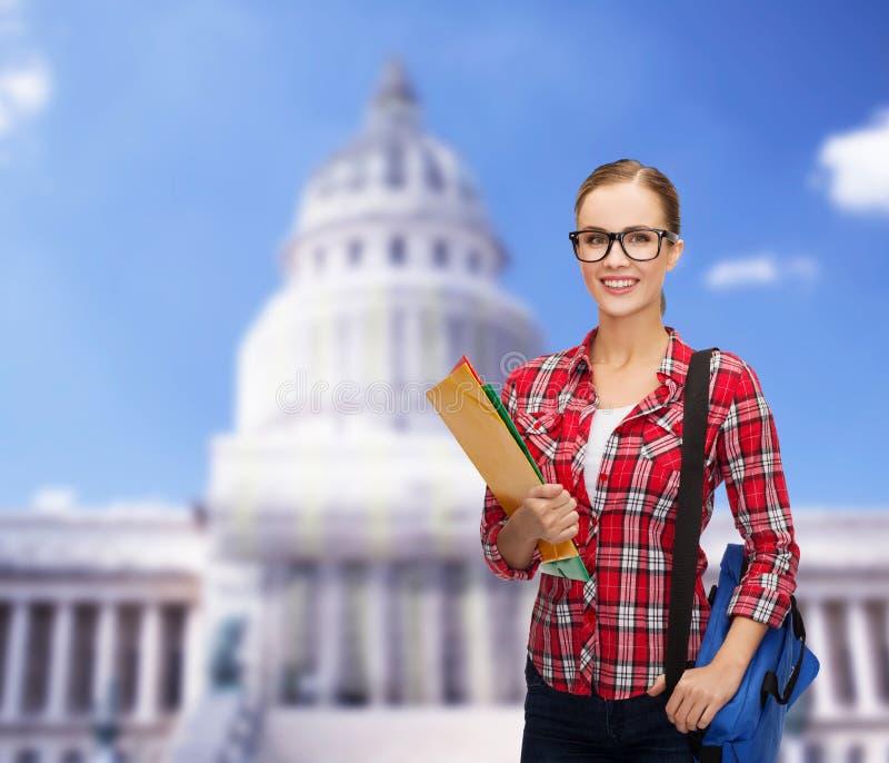 Studentin in den Brillen mit Tasche und Ordnern lizenzfreies stockbild