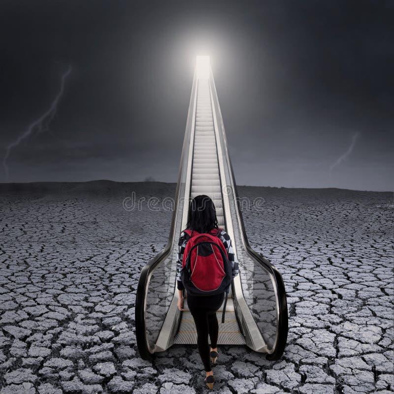 Studentin, die auf der Rolltreppe steigert lizenzfreies stockfoto