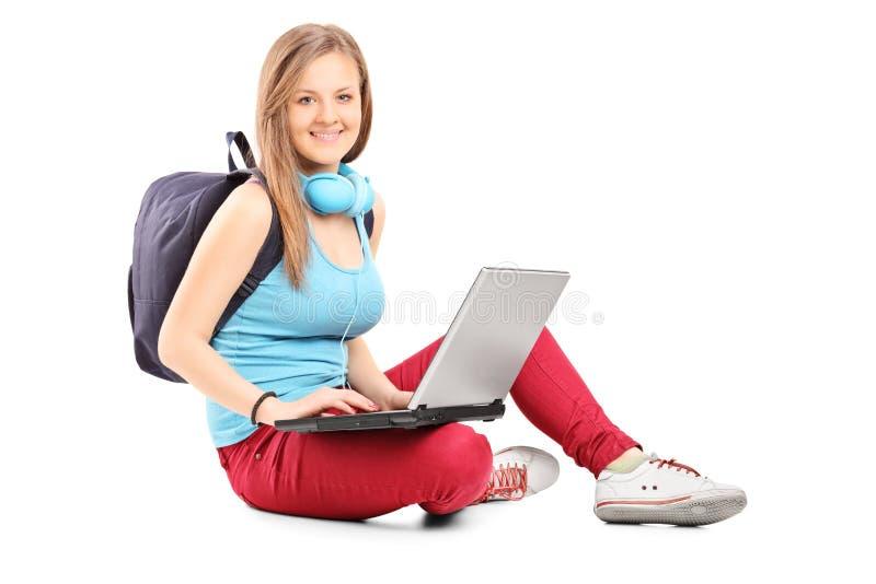 Studentin, die an dem Laptop gesetzt auf dem Boden arbeitet lizenzfreie stockfotos