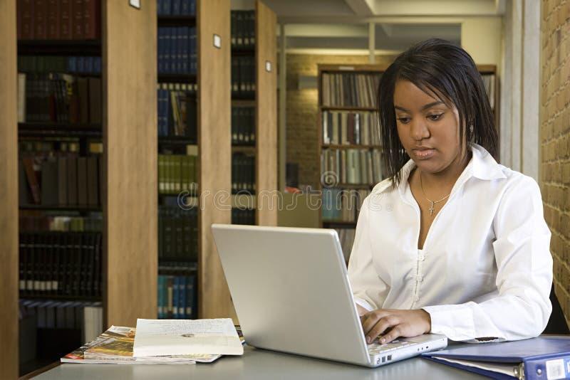 Studentin, die in der Bibliothek arbeitet lizenzfreies stockfoto