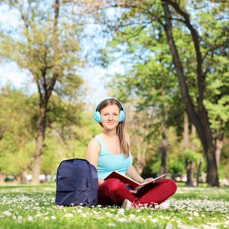 Studentin, die ein Buch im Park liest stockfotos