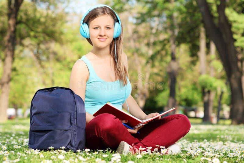 Studentin, die ein Buch im Park liest lizenzfreies stockbild
