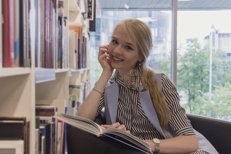 Studentin, die in einem Stuhl mit seiner Hand liest ein Buch, lächelnd am Hintergrund des Bücherschranks und des Fensters sitzt C stockbild