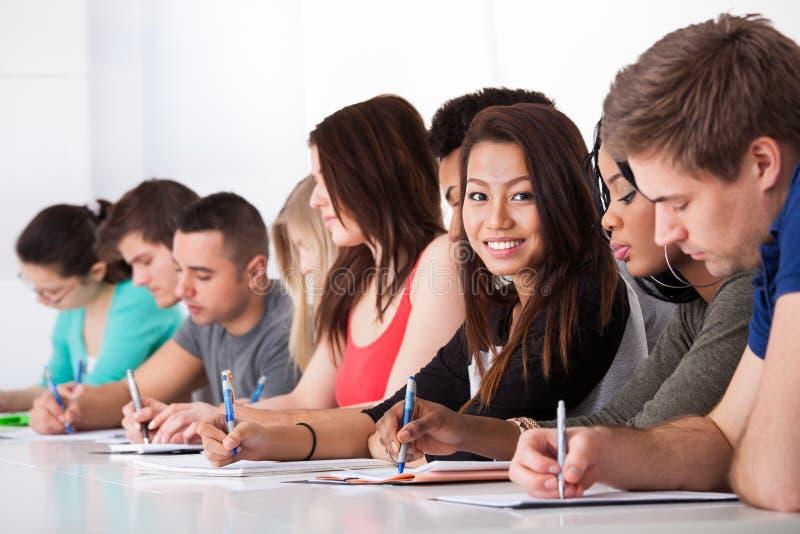 Studentin, die mit den Mitschülern schreiben am Schreibtisch sitzt stockfotografie