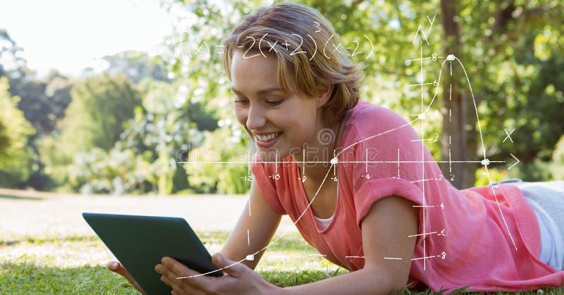 Studentin, die Tablet-PC beim Lügen auf Gras verwendet stockbild