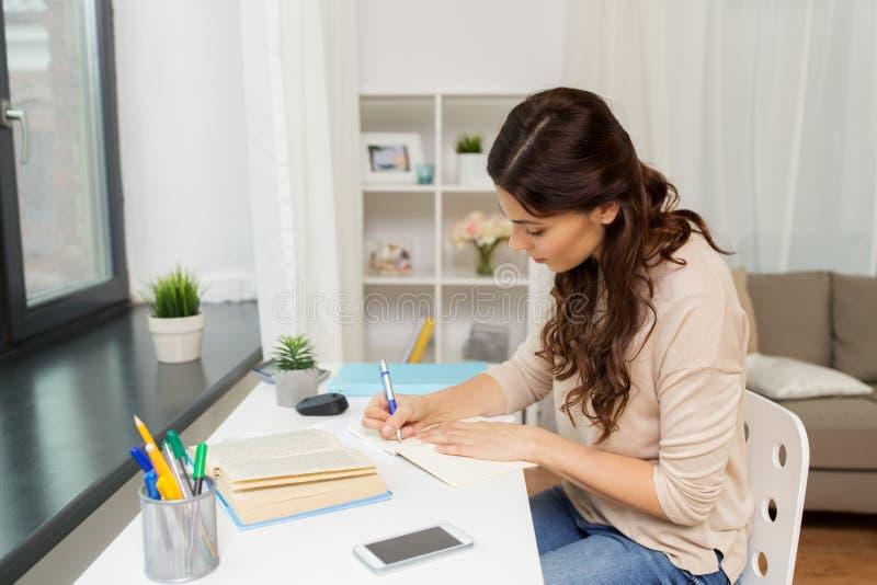 Studentin mit dem Buchlernen zu Hause stockbilder