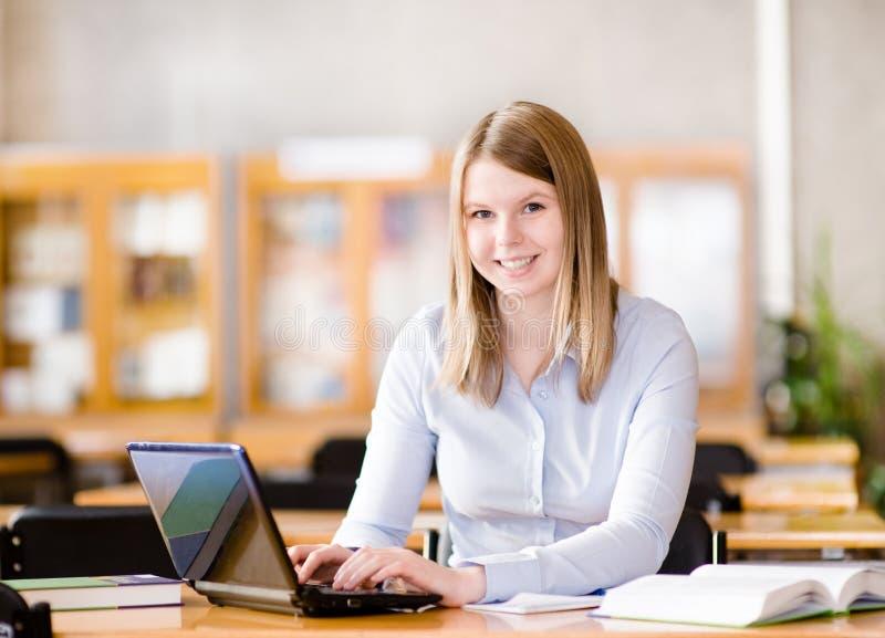 Studentin mit dem Laptop, der in der Bibliothek arbeitet stockbild