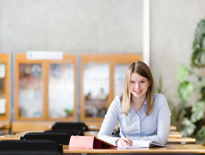 Studentin mit dem Laptop, der in der Bibliothek arbeitet lizenzfreies stockbild