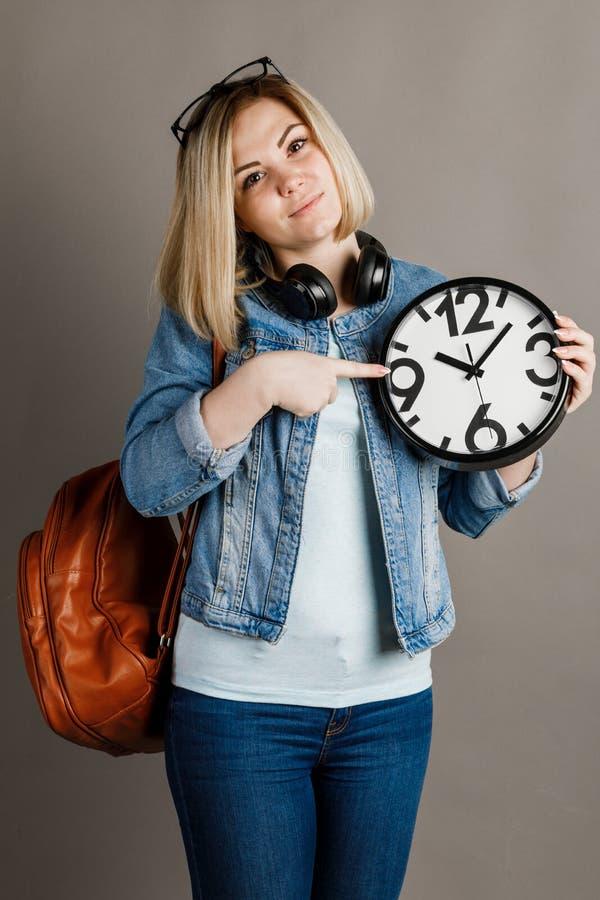 Studentin mit einer großen Uhr in den Händen auf einem grauen Hintergrund lizenzfreie stockfotos
