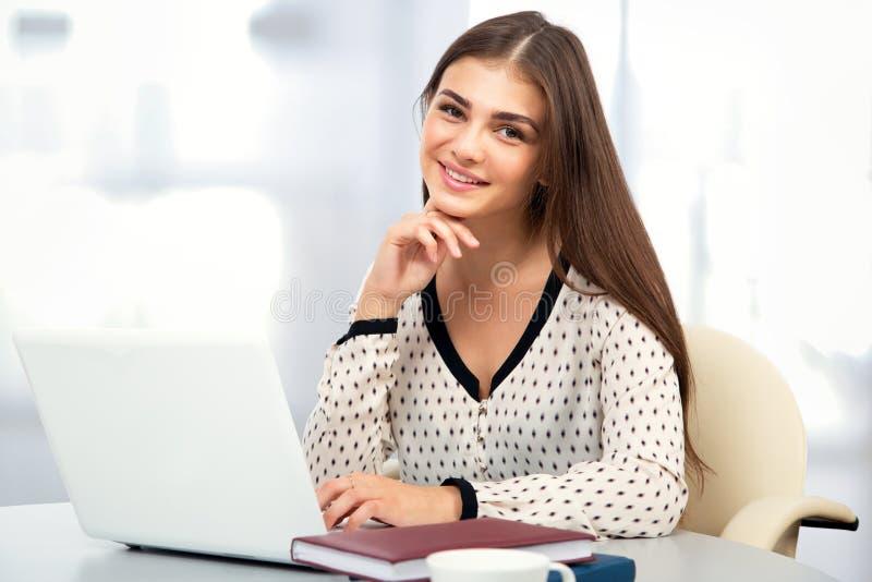 Studentin mit Laptop in einer hohen Schulbibliothek stockbild
