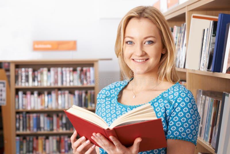 Studentin-Reading Book In-Bibliothek lizenzfreie stockfotografie