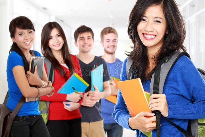 Studentin und Freunde, die zur Kamera lächeln lizenzfreie stockfotografie