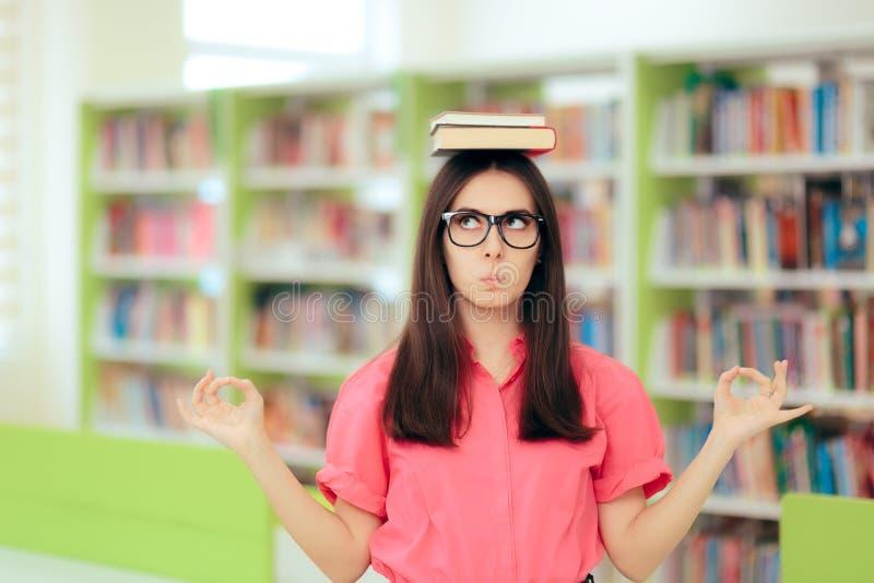 Studentin Writing eine Versuch-Aufgabe in der Schulbibliothek stockfotografie