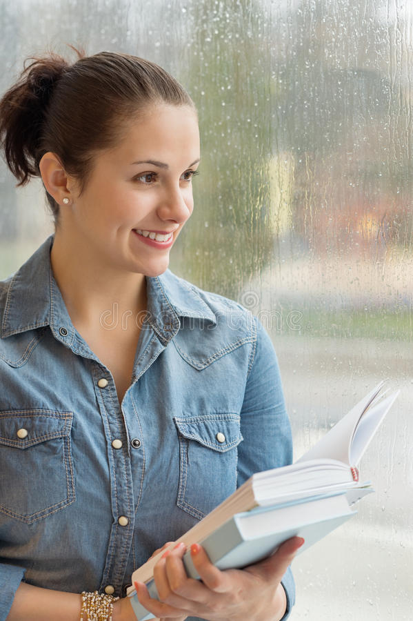Studentinnehavböcker vid det våta fönstret royaltyfria bilder