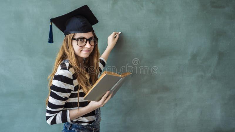 Studentinschreiben auf grüner Tafel lizenzfreie stockfotografie