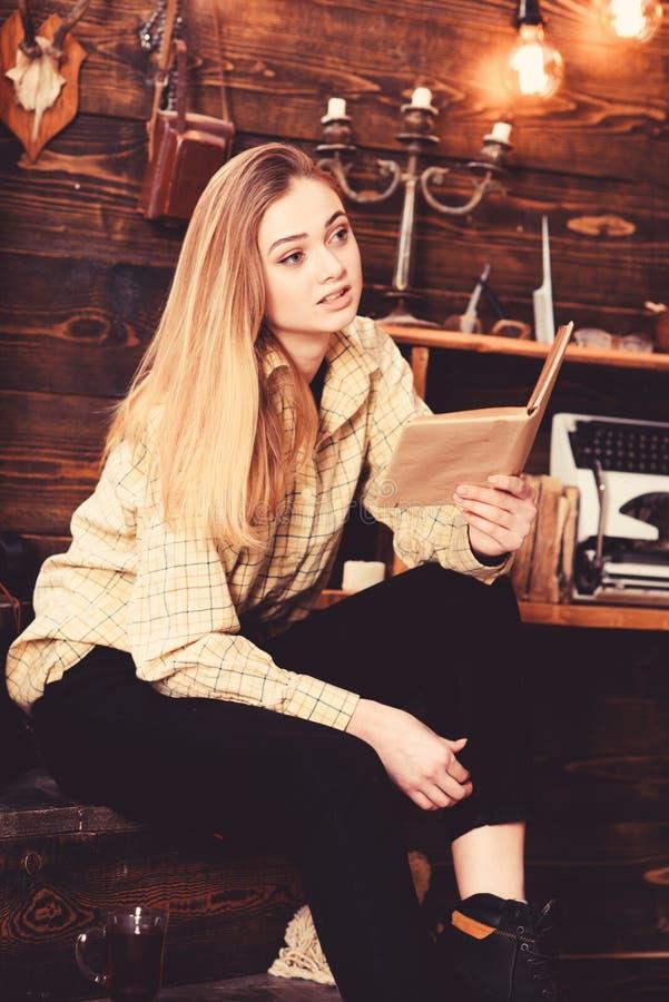 Studentinstudie mit Buch im Haus des Wildhüters Dame auf ruhigem Gesicht in der Plaidkleidung schaut nett und zufällig Mädchen he stockbild