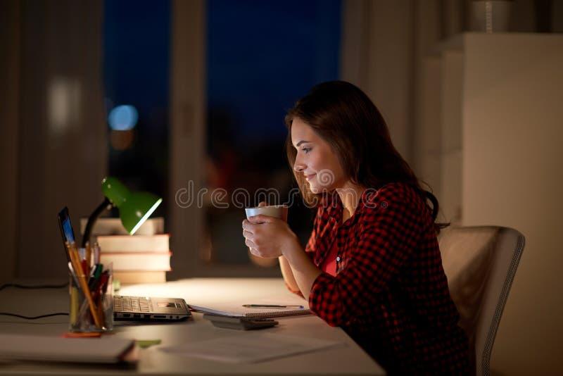 Studentkvinna med bärbara datorn och kaffe på natthemmet royaltyfri bild