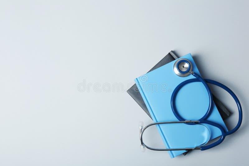 Studentläroböcker, stetoskop och utrymme för text på grå bakgrund arkivbilder