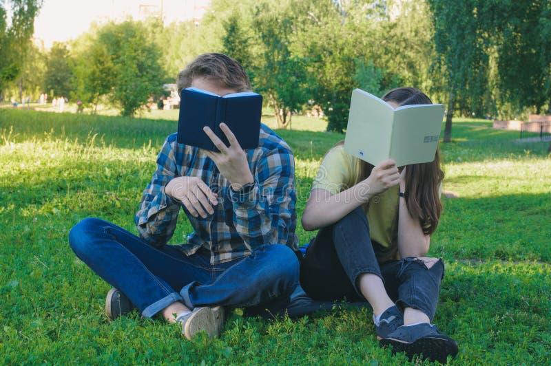 Studentläseböcker Tonåringar som döljer framsidor som behing böcker royaltyfria foton