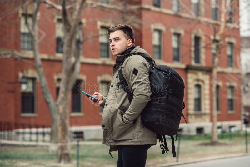 Studentmantext på mobiltelefonen som går i stadshögskolauniversitetsområde med ryggsäcken royaltyfri fotografi