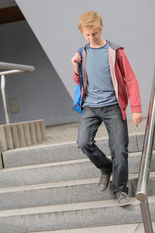 Studentpojke som går ner universitettrappa royaltyfria foton