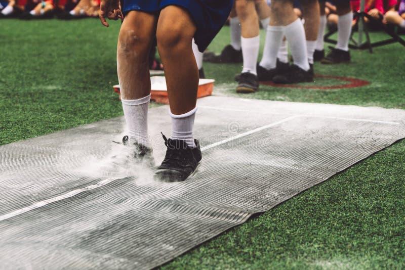 Studentpojke som tar längdhopp på luften under en dag för skolasportkonkurrens royaltyfria bilder